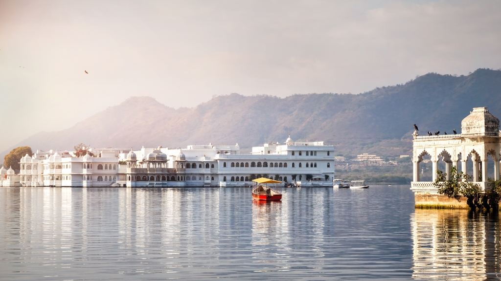 White palace and boat on Lake Pichola in Udaipur, Rajasthan, India