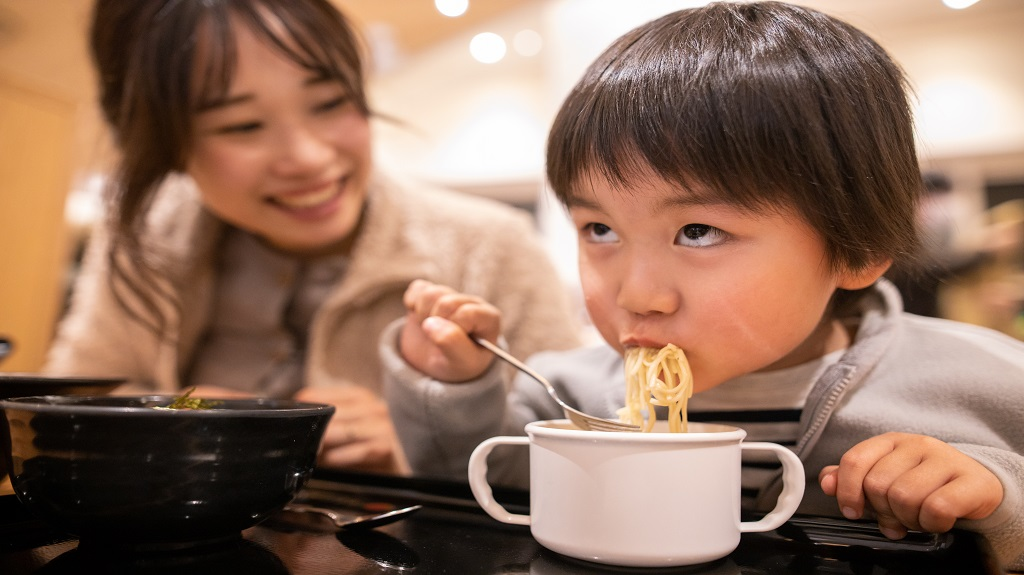 Little boy making a face and eating ramen noodle in food court