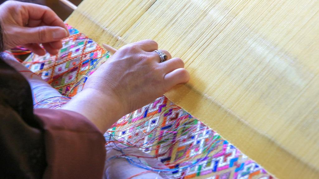 Woman hand-weaving weaving a traditional fabric in downtown Thimphu, Bhutan.
