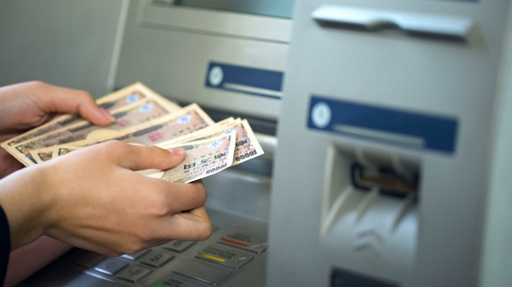 Woman counting Japanese Yen withdrawn from ATM, 24 hours service, easy banking